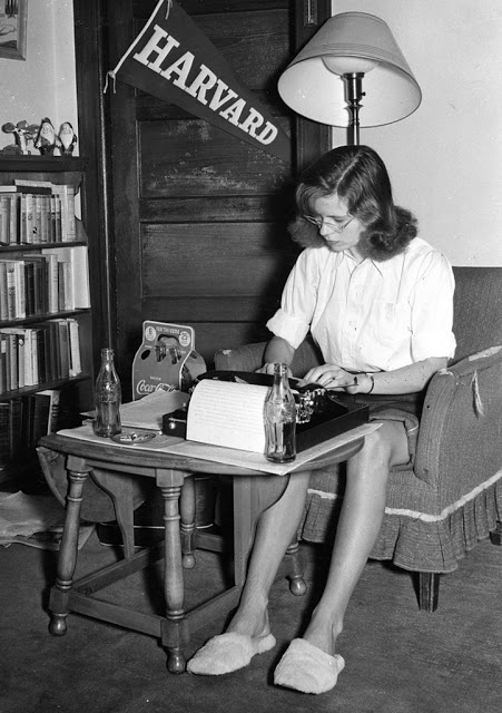 Woman busily working on a typewriter whilst sat in an armchair. The 5 coke bottles around her imply she