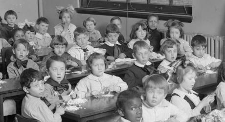 Victorian school kids, some with hair-bows as big as their heads, and lots of frills on their clothes. All crammed into a class room, cutting pieces of paper at the same time as looking bemused by the camera in their classroom