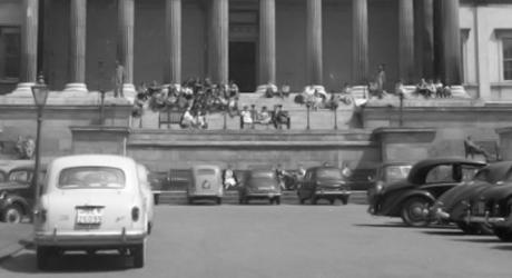 Students eating on the steps of an old stone building, with old cars parked in the carpark in the foreground.