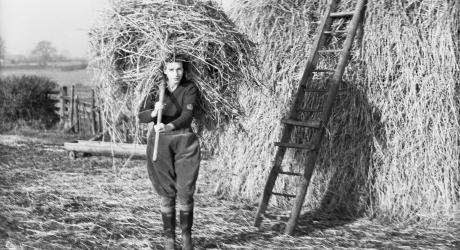 A girl carrying a fork full of hay