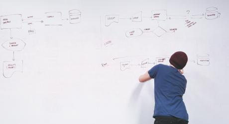 A man drawing a flow chart on a huge whiteboard