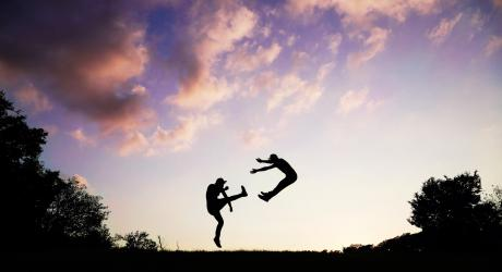 Silhouette of two people fighting