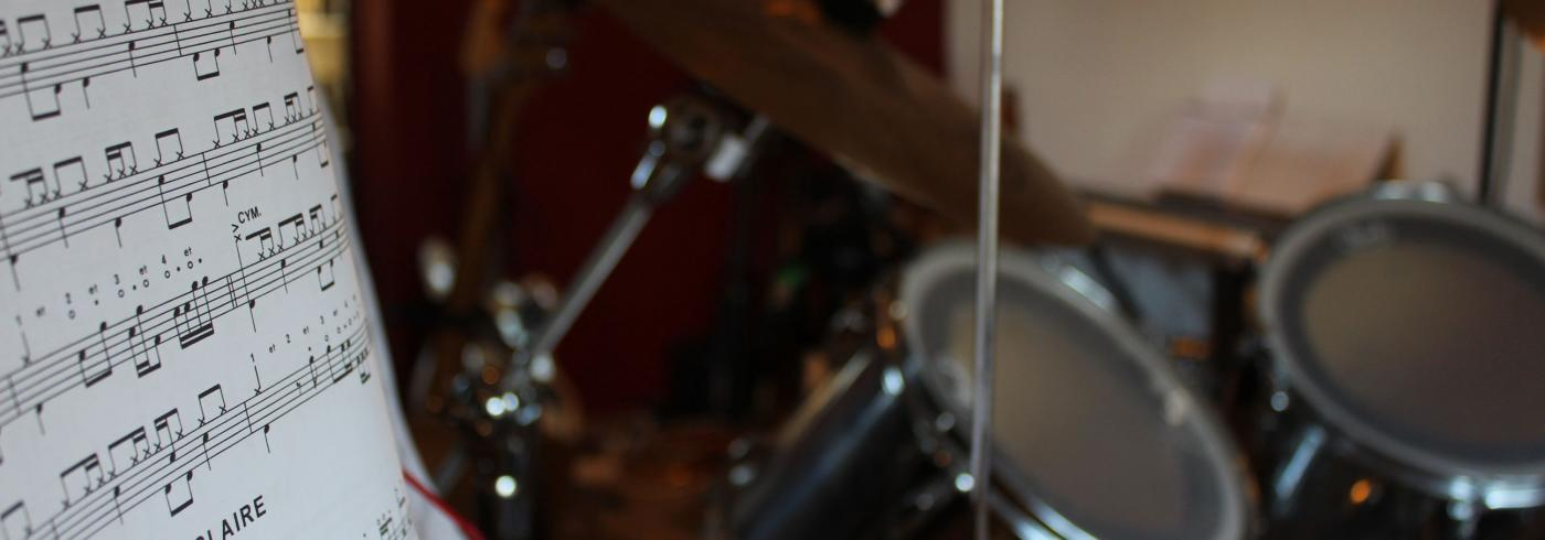 Sheet music and drum kit in a studio.