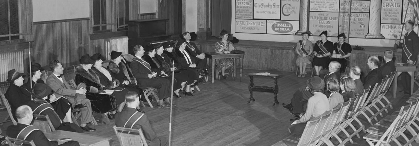 Smartly dressed people sat on fold-out chairs, in a rows facing each other in a timber clad town hall, with three women at the front looking very happy. Some empty chairs in the audience, like they were expecting a bigger turnout.