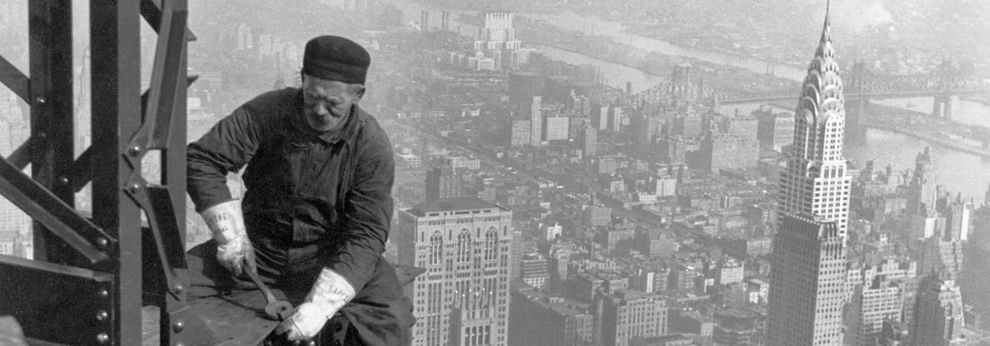A male construction worker sitting on the edge of a steel beam high up, against a New York skyline.