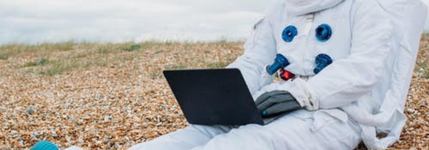 An astronaut sitting on a beach with a laptop