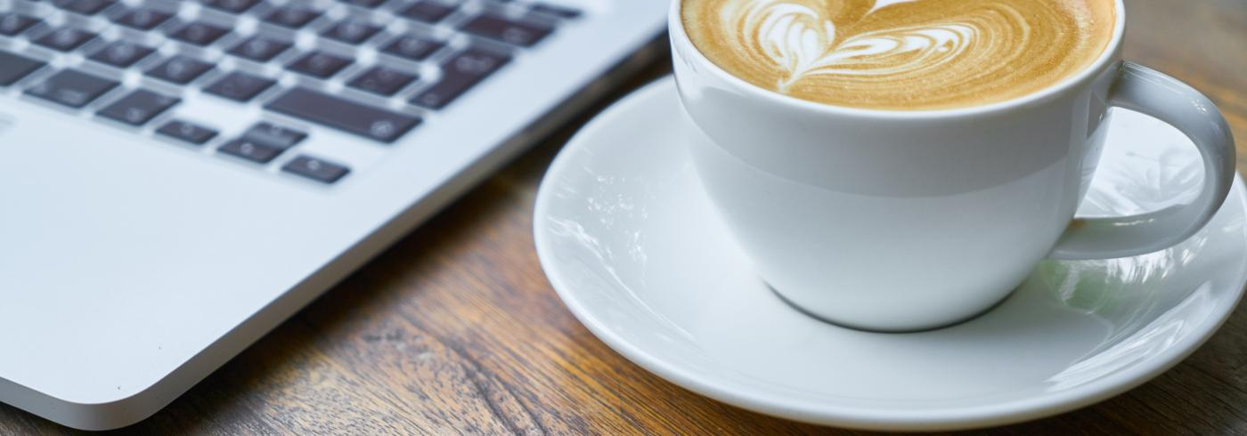 A coffee on a wooden table next to a laptop
